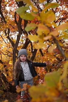 Schattige jongen meisje 4-5 jaar oud trui en jas dragen in park. camera kijken. herfstseizoen. jeugd. modieuze stijlvolle en charmante kleine dame