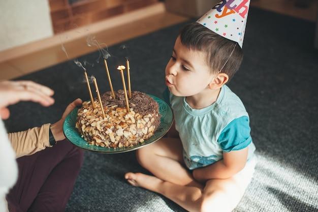 Schattige jongen met feestmuts blaast de lichten op de taart terwijl moeder het bord vasthoudt