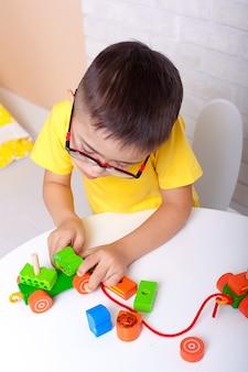 Schattige jongen met het syndroom van down spelen in de kleuterschool.