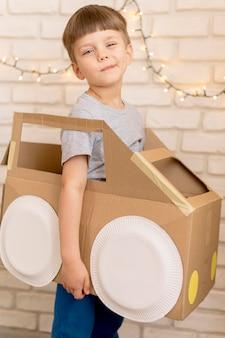 Schattige jongen met kartonnen auto
