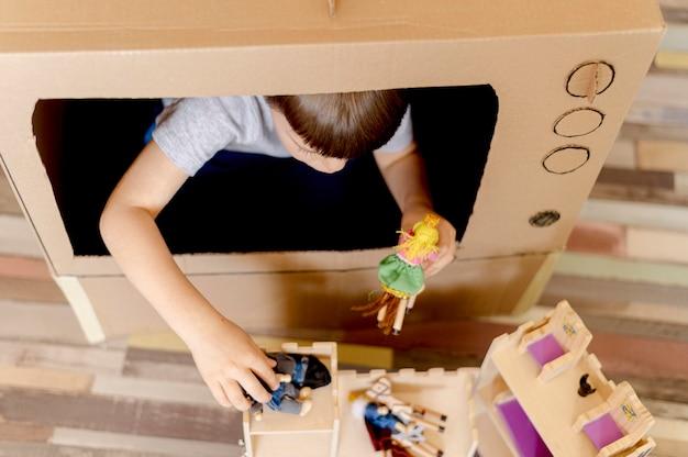 Schattige jongen met kartonnen tv close-up