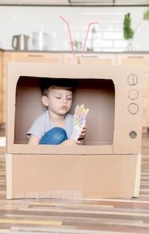 Schattige jongen met kartonnen tv