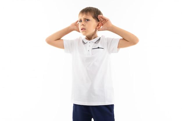 Schattige jongen met pony in een wit t-shirt luistert naar de geluiden op een witte achtergrond met kopie ruimte