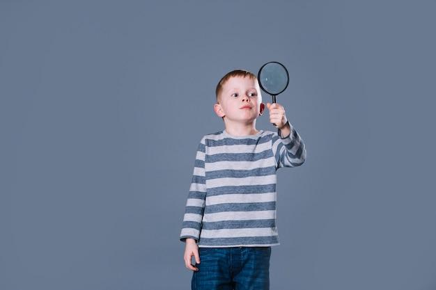 Schattige jongen met vergrootglas