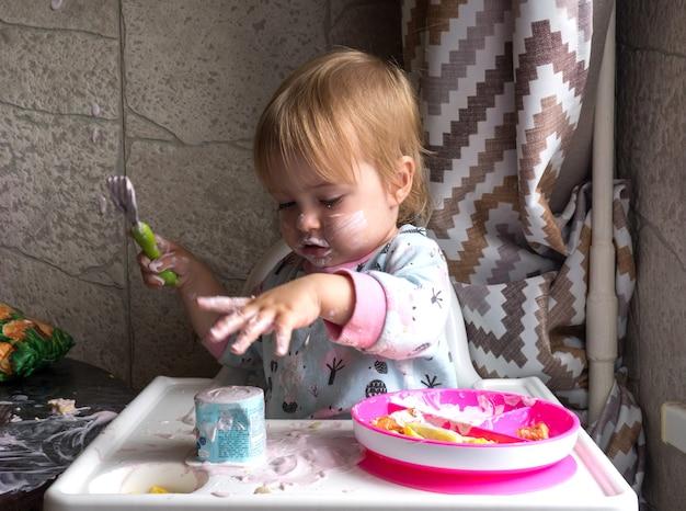 Schattige jongen met vies gezicht thuis ontbijten en een vork in zijn hand houden