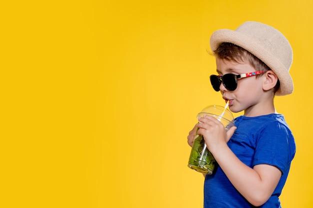 Schattige jongen mojito cocktail drinken uit plastic beker over gele studio achtergrond.