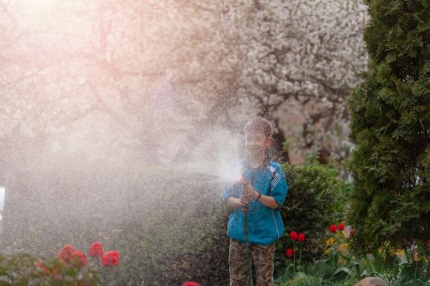 Schattige jongen planten water geven uit de slang, maakt een regen in de tuin. kind dat ouders helpt om bloemen te kweken.