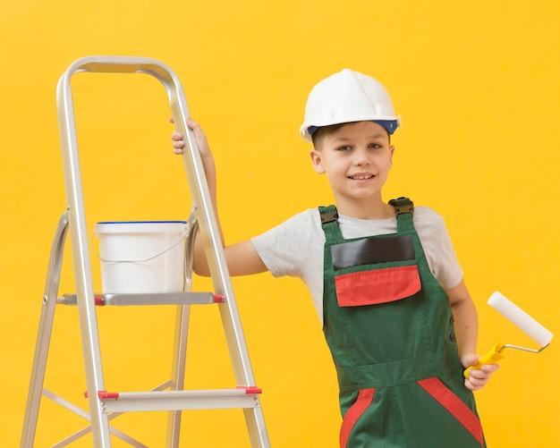Schattige jongen poseren met ladder