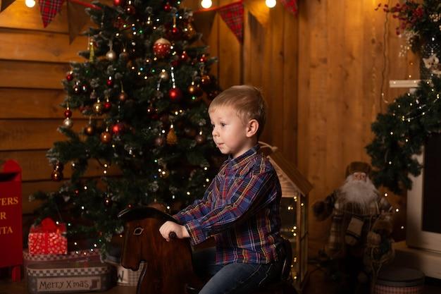 Schattige jongen rijden houten traditioneel hobbelpaard speelgoed in de buurt van de kerstboom feestelijk ingericht huis