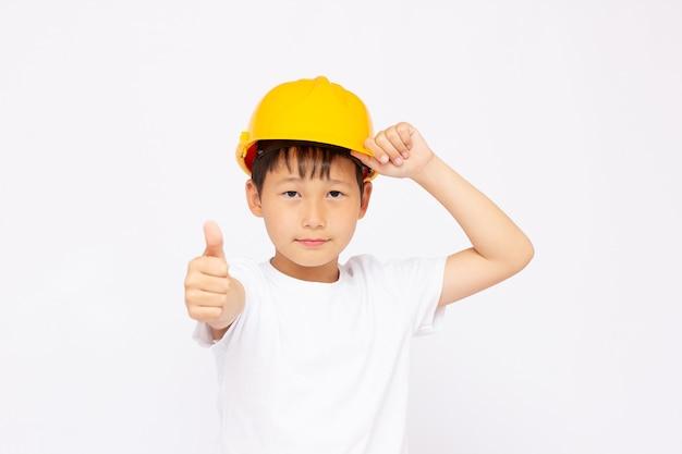 Schattige jongen tijdens het dragen van bouwhelm, geïsoleerd op een witte achtergrond