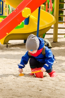 Schattige jongen van twee jaar in een blauwe jas en rode sjaal speelt op een lichte speeltuin met een lepel en een emmer
