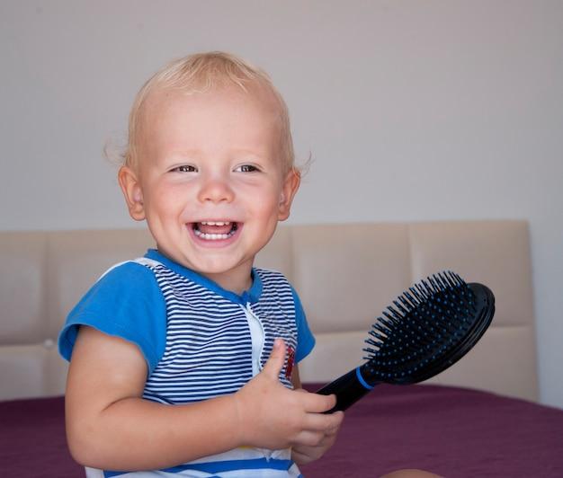 Schattige jongen zijn haren borstelen. schattige baby plezier, houden een haarborstel en kammen zijn haar.