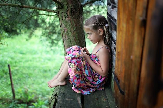 Schattige jongen zit alleen in de boomhut in de zomer