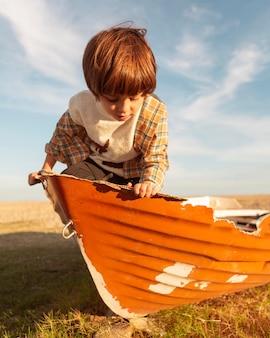 Schattige jongen zit in boot middelgroot schot