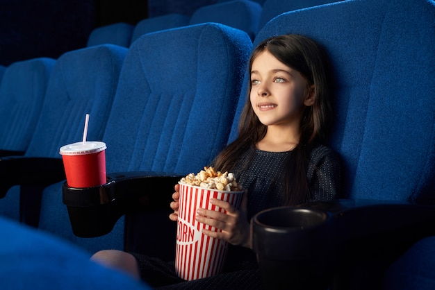 Schattige jongen zitten met popcorn emmer in de bioscoop.