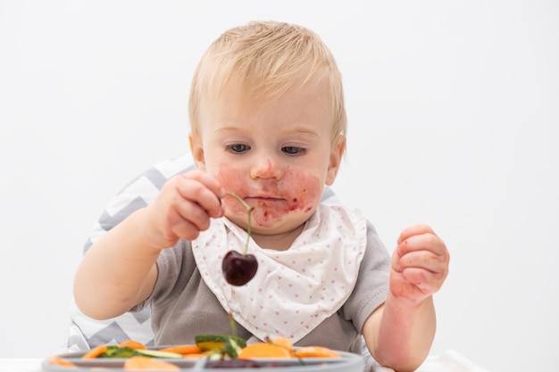 Schattige kaukasische baby van ongeveer 1 jaar oud die verse groenten eet in de kinderstoel zelfvoeding voor kinderen babyled-speenidee gezonde voeding van vast voedsel voor baby's