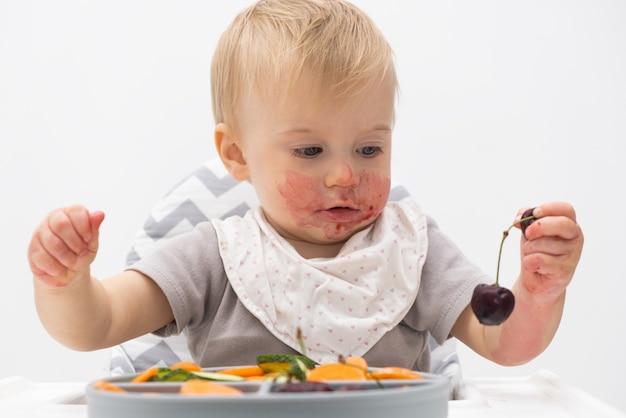 Schattige kaukasische baby van ongeveer 1 jaar oud die verse groenten fruit eet in de kinderstoel zelfvoeding voor kinderen babyled speenidee gezonde voeding van vast voedsel voor baby's