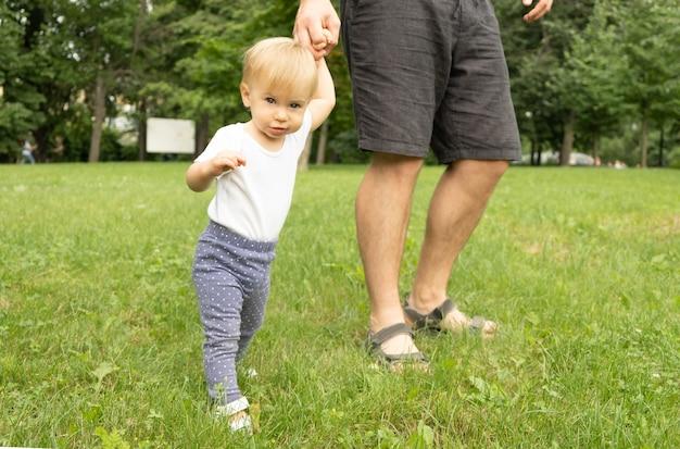 Schattige kaukasische blonde baby staande op gras hand in hand van onherkenbare man, camera kijken. vader en kind wandelen in de weide. ouder en kind, tijd samen doorbrengen buitenshuis.