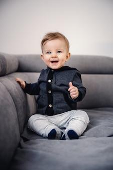 Schattige kaukasische blonde kleine jongen met blauwe ogen lachen en zittend op de bank in de woonkamer.