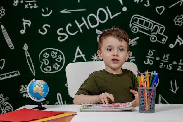 Schattige kind jongen huiswerk. slimme jongen tekenen aan balie. schooljongen. basisschool student tekenen op de werkplek. kinderen genieten van leren. thuisonderwijs. terug naar school. kleine jongen op schoolles