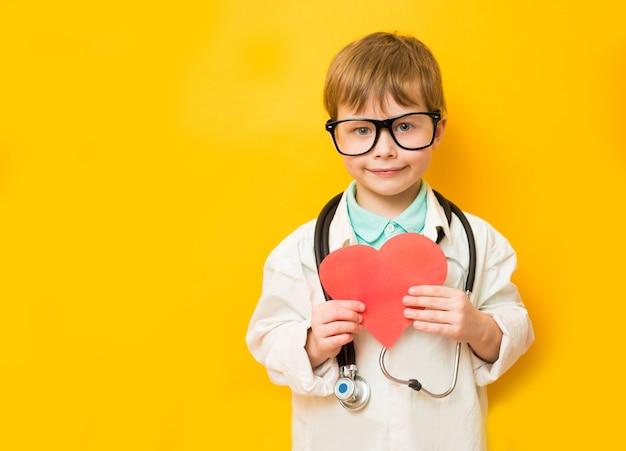 Schattige kind jongen in doktersuniform met stethoscoop en hart in de hand op gele achtergrond. ruimte kopiëren