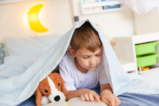 Schattige kind jongen leest een boek liggend op het bed in zijn kamer