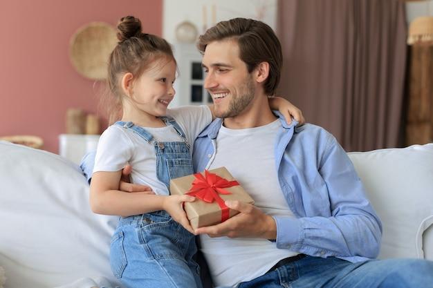 Schattige kinderdochter verrast papa, klein meisje presenteert geschenkdoos aan vader die op de bank zit. vaderdag.
