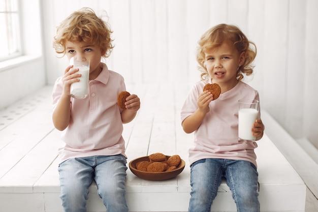 Schattige kinderen eten koekjes en consumptiemelk