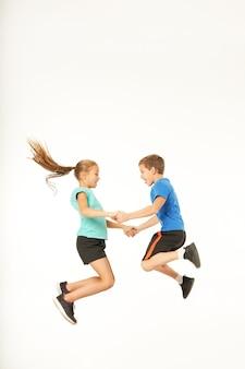 Schattige kinderen hand in hand en springen tegen een witte achtergrond