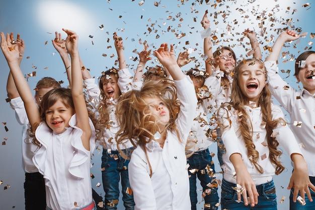 Schattige kinderen hebben plezier samen gooien kleurrijke confetti op verjaardagsfeestje. ze spelen samen in verschillende spellen en brengen tijd door in een ingerichte studio. concept voor kinderen en evenementen
