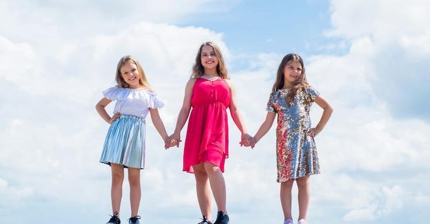 Schattige kinderen in jurk houden elkaars hand vast, vriendschap.