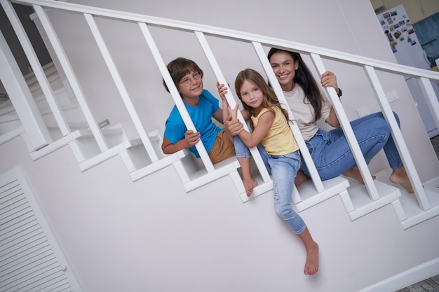 Schattige kinderen kleine jongen en meisje tijd doorbrengen met hun jonge positieve moeder terwijl ze samen zitten op