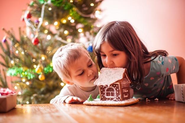 Schattige kinderen knabbelen aan een peperkoekkoekjeshuis met kerst