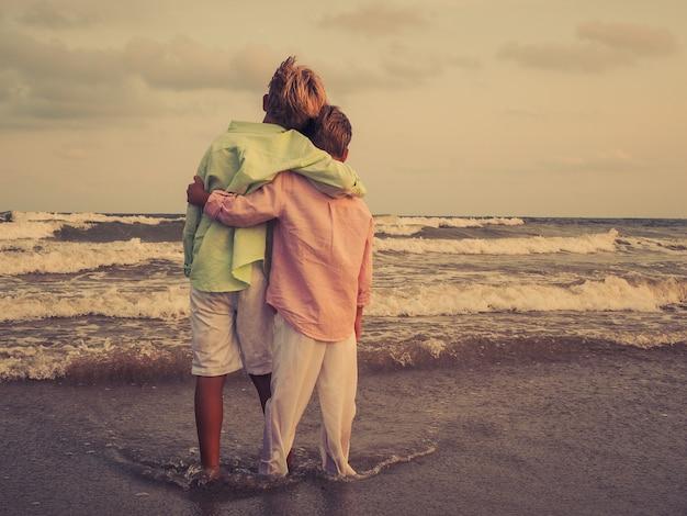 Schattige kinderen knuffelen elkaar op het strand en genieten van het prachtige uitzicht op zee