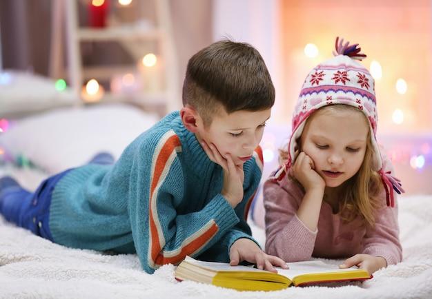 Schattige kinderen lezen een boek op de vloer in de versierde kerstkamer
