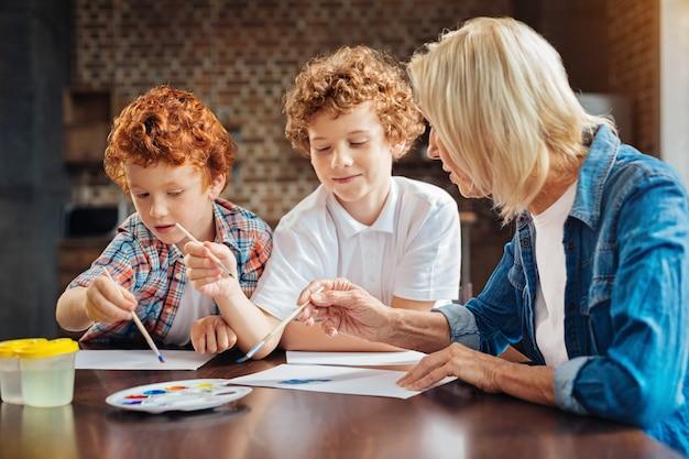 Schattige kinderen met krullend haar richten hun aandacht op hun stukjes papier en luisteren naar hun oma terwijl ze allemaal aan een tafel samenkomen en samen schilderen.