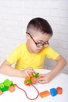 Schattige kinderen met speciale behoeften die spelen met het ontwikkelen van speelgoed terwijl ze aan het bureau in het kinderdagverblijf zitten.