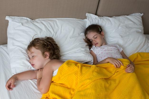Schattige kinderen slapen op het bed