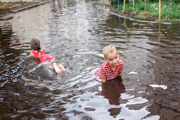 Schattige kinderen springen en zwemmen in de plassen na warme zomerregen gelukkige jeugd
