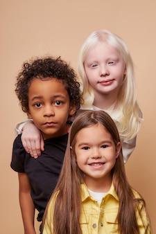 Schattige kinderen van verschillende nationaliteiten en huidskleuren staan samen