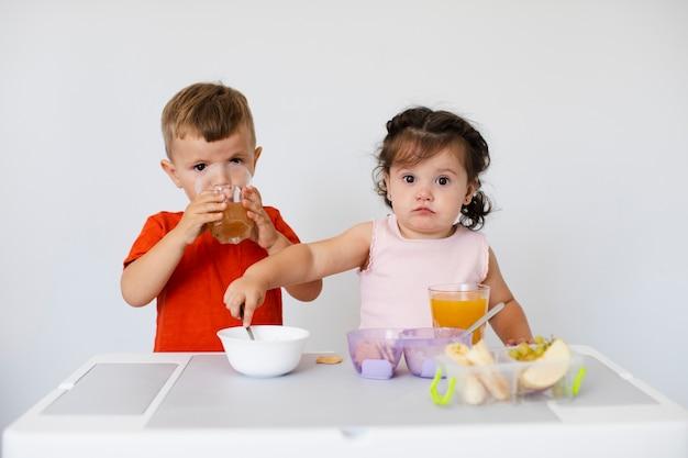 Schattige kinderen zitten en genieten van hun snacks
