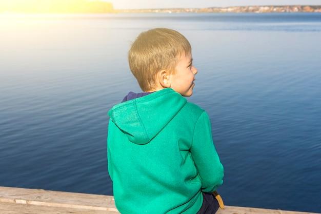 Schattige kindjongen kijkt in de verte van het meer. herfst landschap. peinzend denkend kind. jonge reiziger