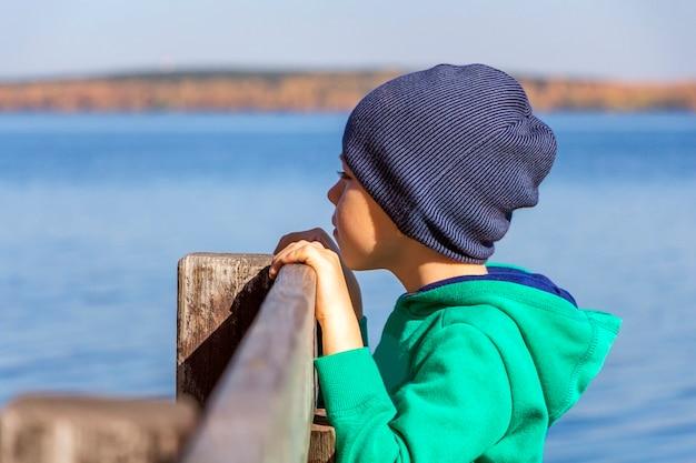 Schattige kindjongen kijkt in de verte van het meer. herfst landschap. peinzend denkend kind