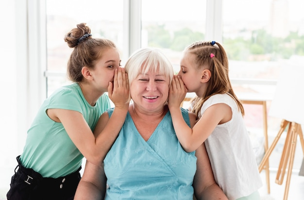 Schattige kleindochters die geheim delen met grootmoeder Premium Foto