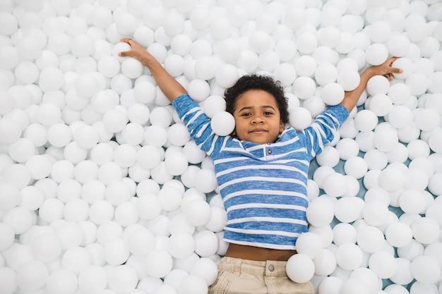 Schattige kleine afrikaanse jongen in vrijetijdskleding armen verhogen terwijl plezier tussen witte ballonnen tijdens spelen geïsoleerd