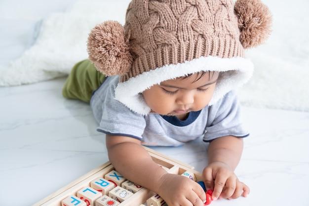 Schattige kleine asin babyjongen spelen met houten speelgoed