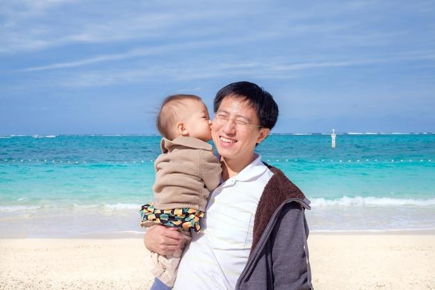 Schattige kleine aziatische 1 jaar oude / 18 maanden peuter baby jongen kind kus vader op een prachtig wit zandstrand