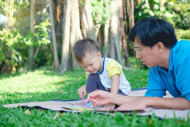 Schattige kleine aziatische 2 - 3 jaar oude peuter jongen kind schilderij met kleurpotloden