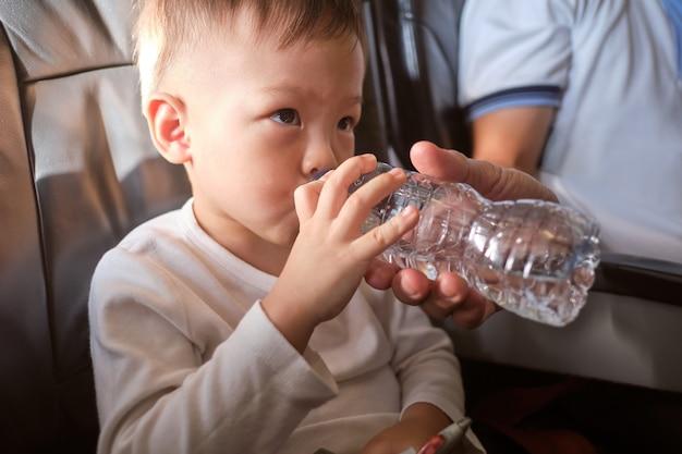 Schattige kleine aziatische 3 jaar oude peuter jongen kind drinkwater uit de fles tijdens de vlucht in het vliegtuig