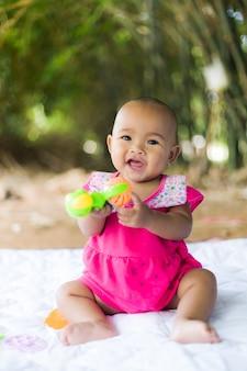 Schattige kleine aziatische baby zitten en spelen met geluk